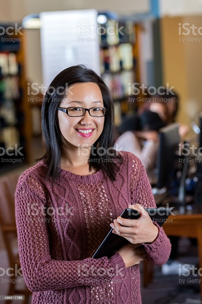 Young Asian college student working in school library stock photo