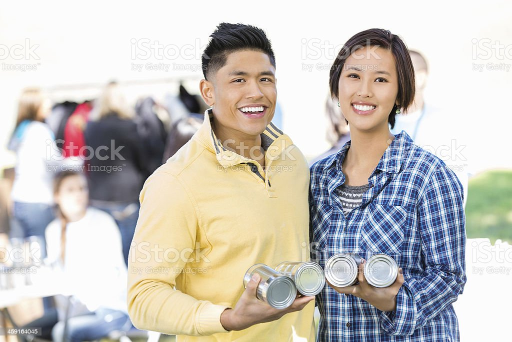 Young Asian couple donating food together at donation drive stock photo