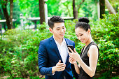 Young Asian Couple Editing Just Made Photos on Smartphone