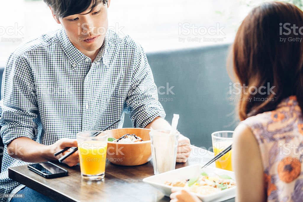 Young asian couple having lunch in cafe. stock photo