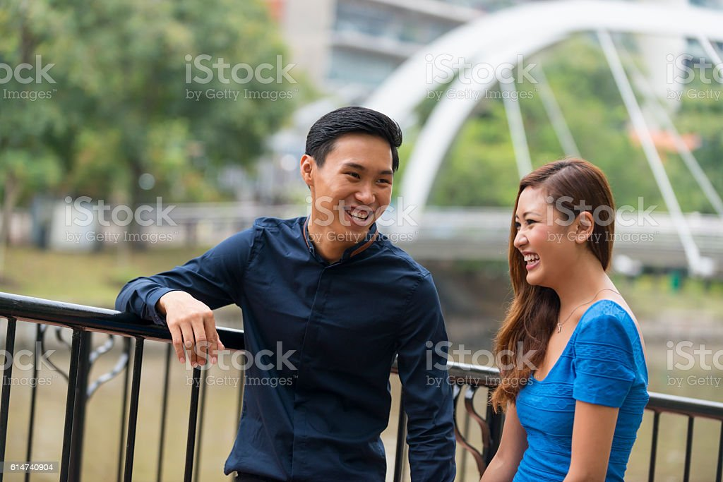Young Asian Couple Scrolling in City Park stock photo