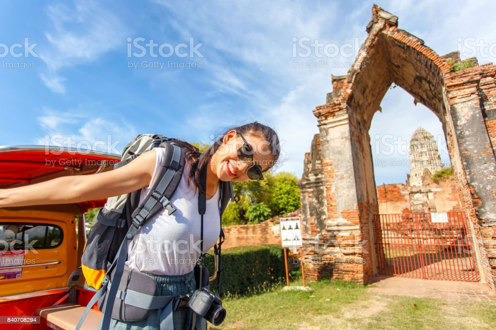 Young asian female traveler with backpack traveling with standing on taxi or Tuk Tuk and happy fun with old temple (Wat Mahathat) background, Ayutthaya Province, Thailand stock photo
