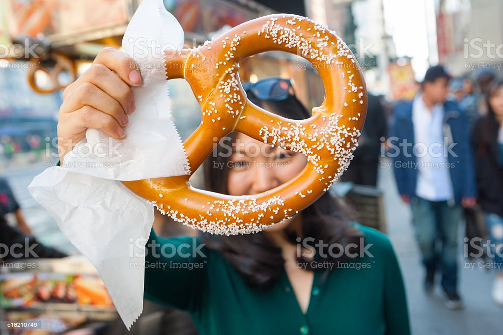 Young asian girl holding pretzel in NYC stock photo