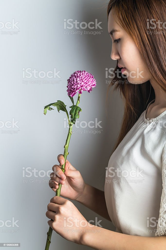 young asian girl holding purple daisy on hand stock photo