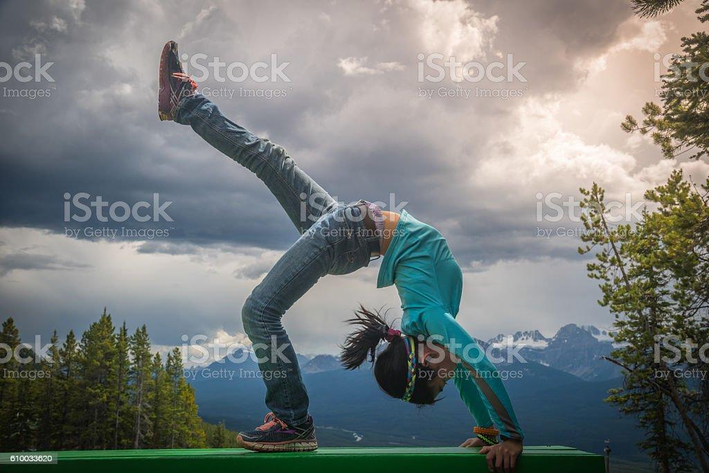 Young asian girl in bridge pose at Lake Louise Area stock photo