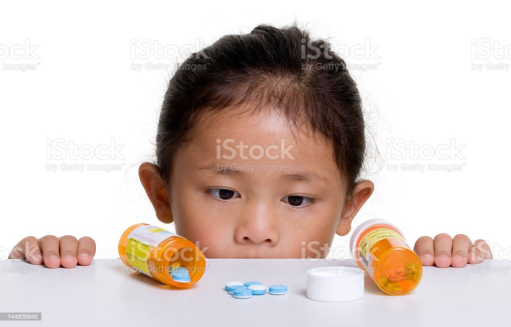 A young Asian girl looking over a counter of open medicine royalty-free stock photo