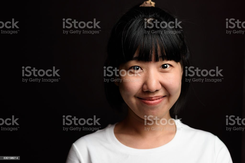 Young asian girl smiles in the black background stock photo