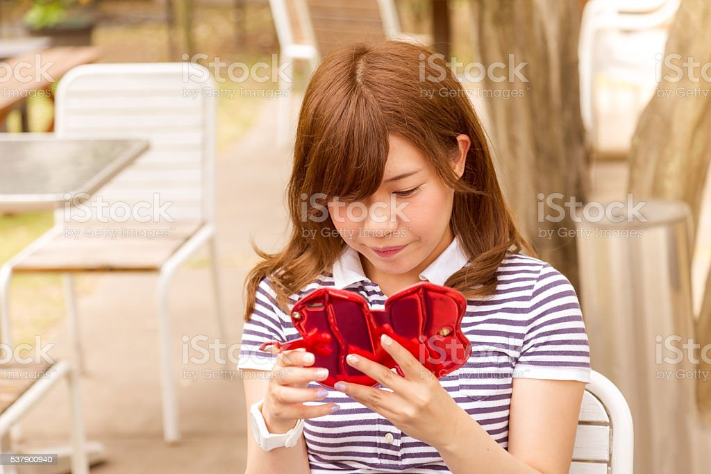 Young Asian Girl Using her Smartphone in a Park stock photo