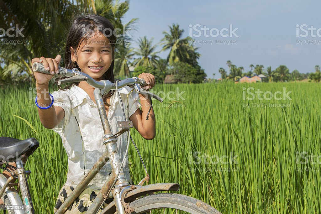 Young Asian girl with bicycle in the rice field stock photo