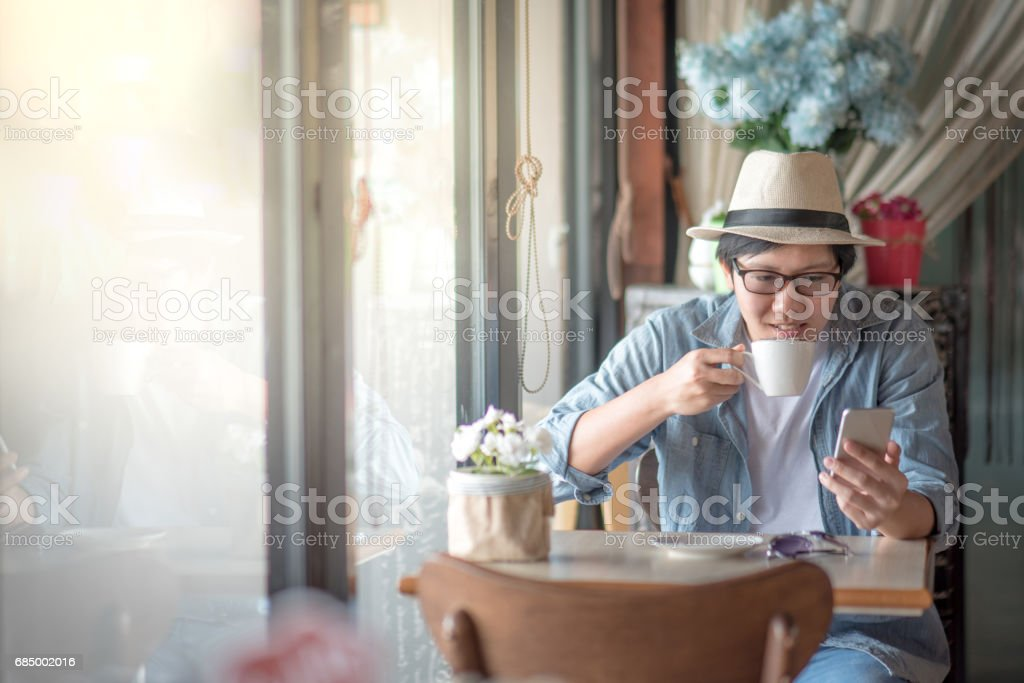 Young Asian happy man text messaging by smartphone during coffee time in cafe stock photo
