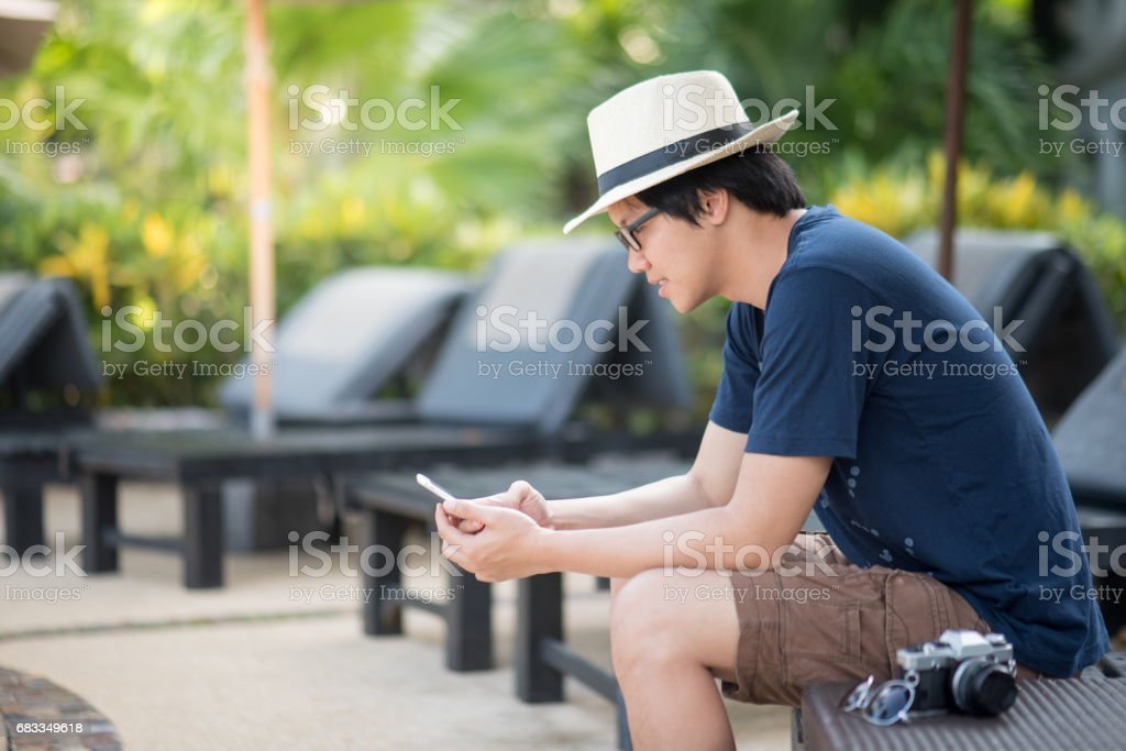 Young Asian happy man text messaging by smartphone in resort stock photo