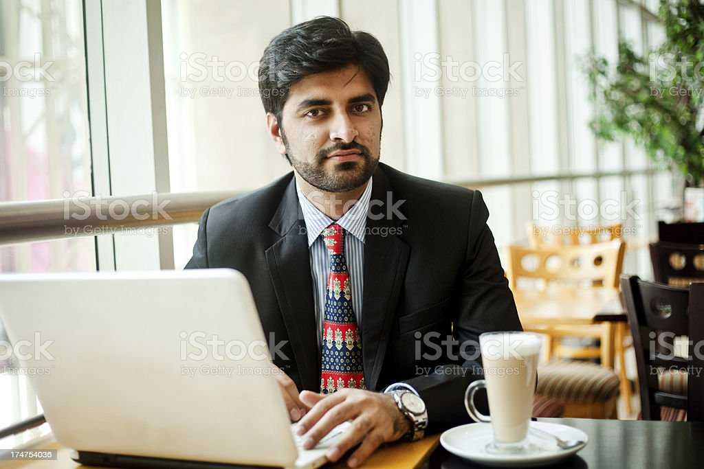 Young Asian Indian Businessman working on laptop in cafeteria royalty-free stock photo