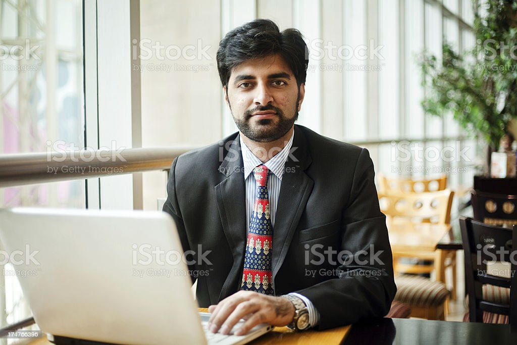 Young Asian Indian Businessman working on laptop in cafeteria stock photo