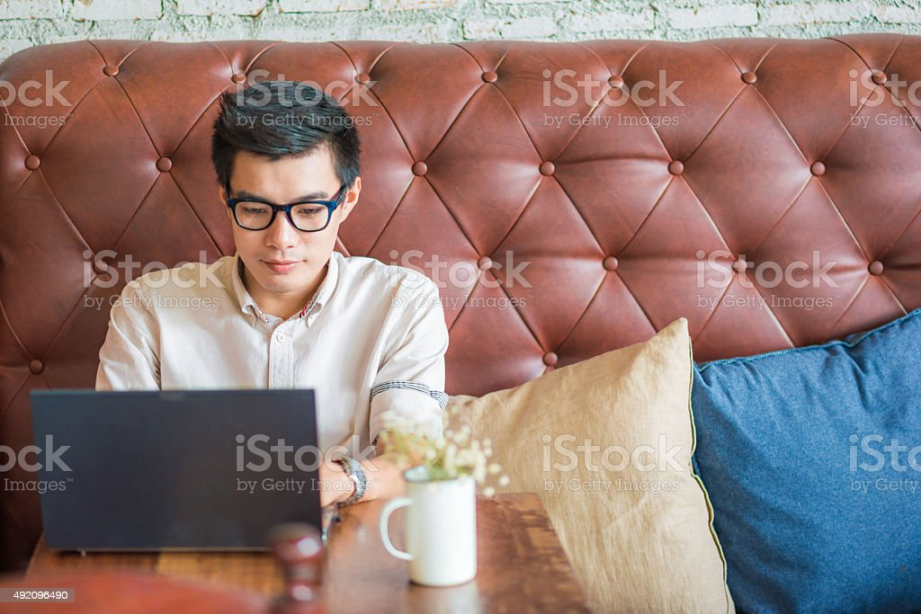 Young asian man drinking coffee cafe and using laptop compute stock photo