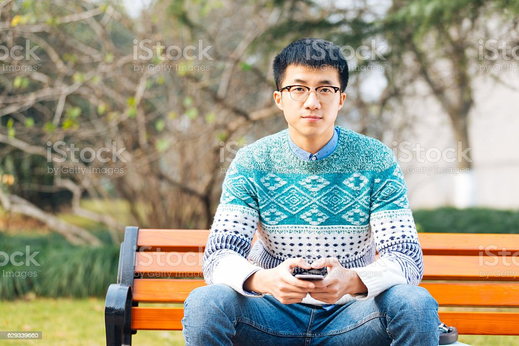 young asian man holds mobile phone stock photo