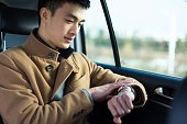 young asian man  looking at watch in car