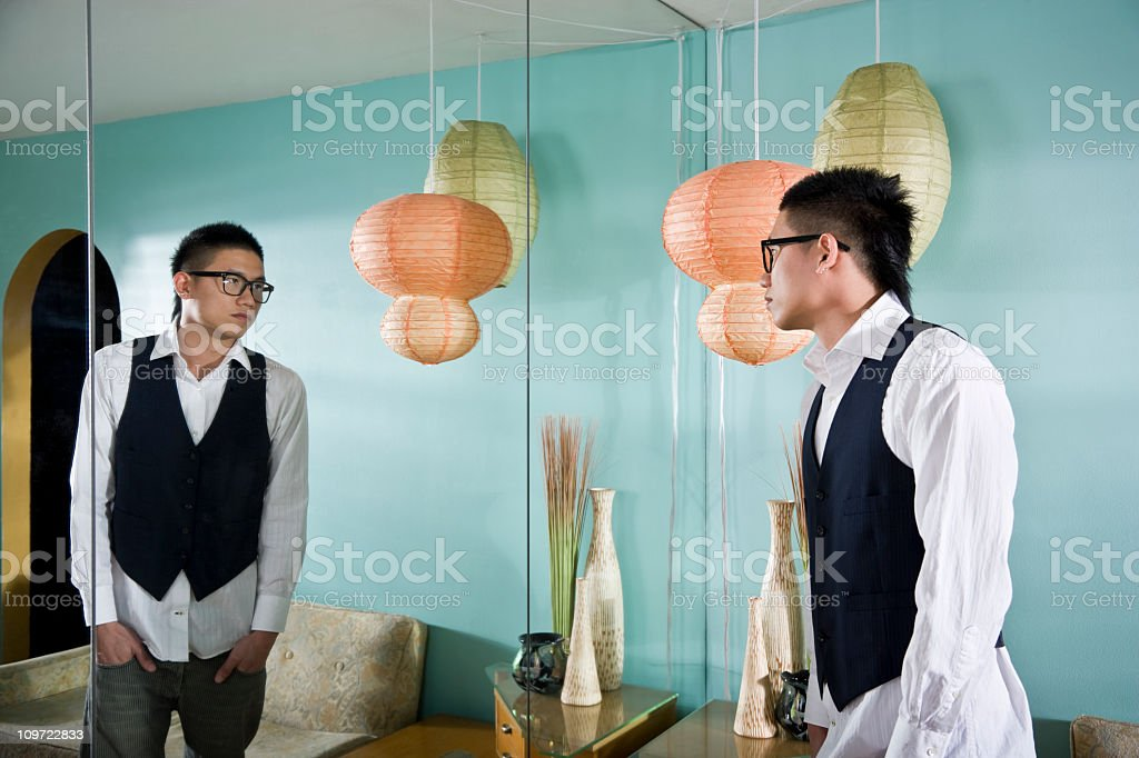 Young Asian man looking in mirror royalty-free stock photo