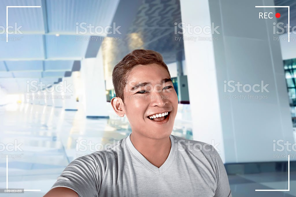 Young asian man pose and take selfie in airport lobby stock photo