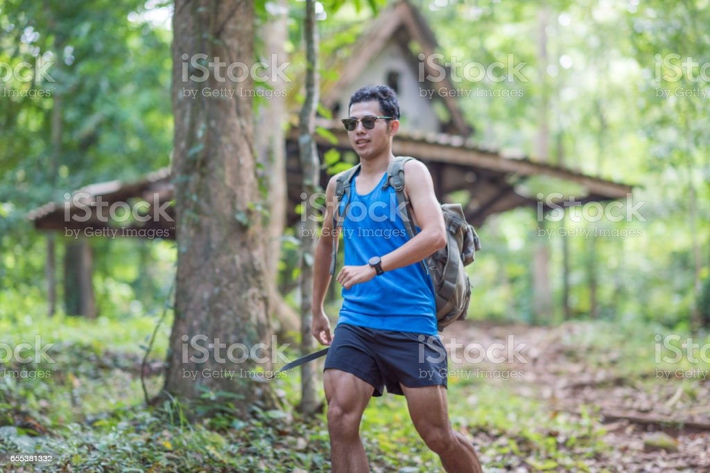 Young asian Man running fitness in tropical forest in summer stock photo