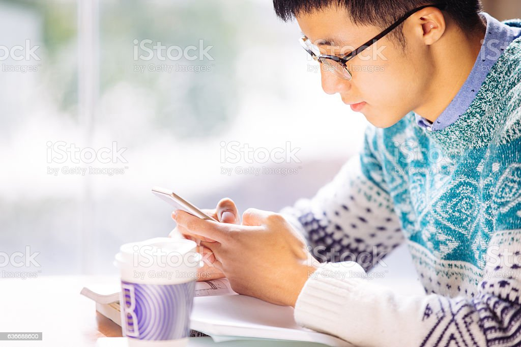 young asian man student holds mobile phone stock photo