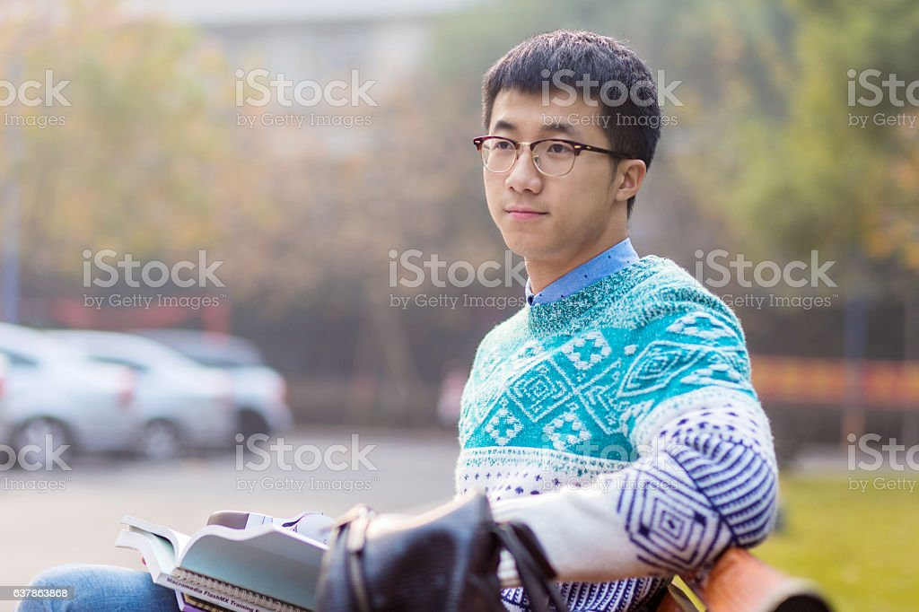 young asian man student reading in park stock photo