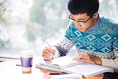 young asian man student studying in library