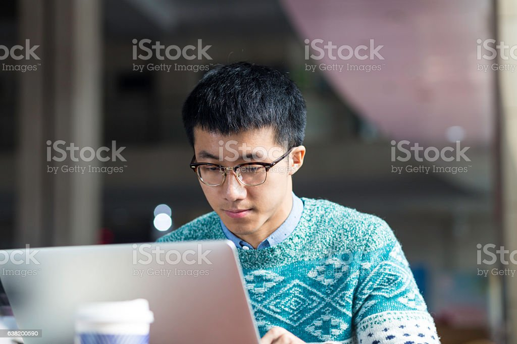 young asian man studying with laptop stock photo