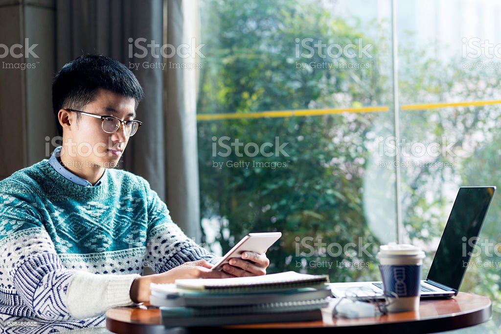 young asian man studying with tablet stock photo