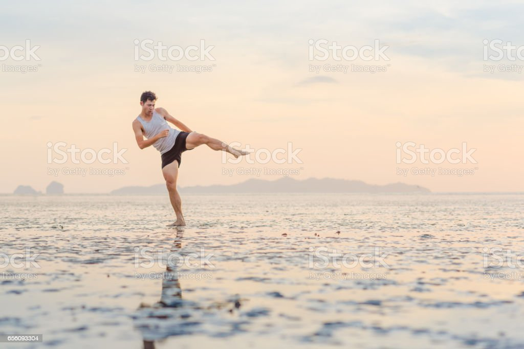 Young asian man training karate and kick boxing at the beach stock photo