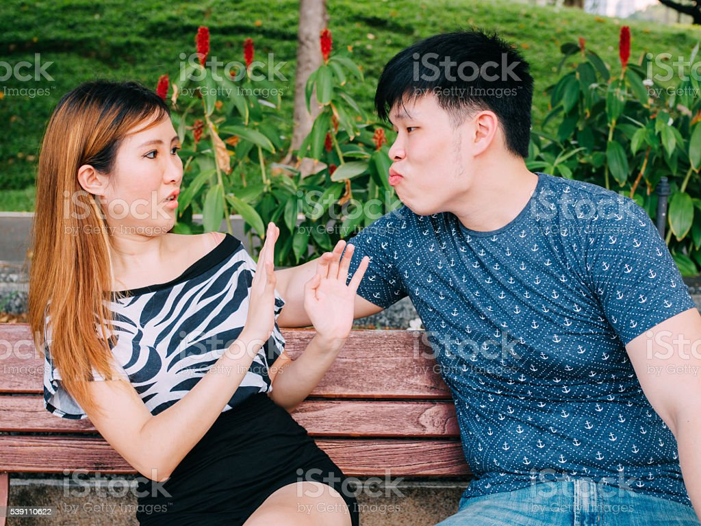 Young Asian man trying to kiss girl & get rejected stock photo