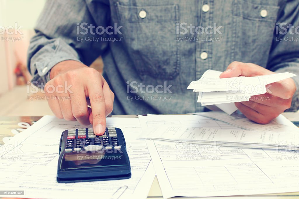 Young asian man using calculator and calculating bills in home stock photo