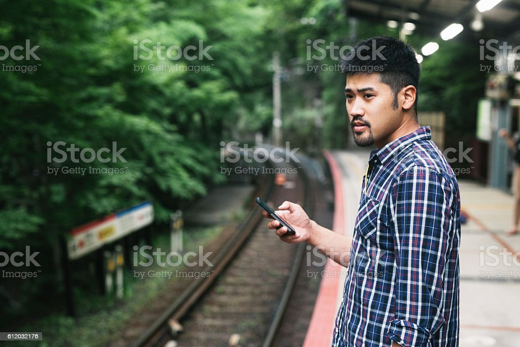 Young Asian Man Waitin for Train, Holding a Phone stock photo