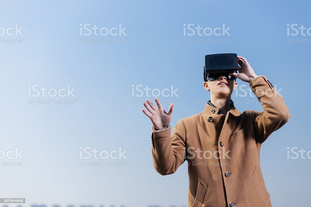 young asian man wearing VR in blue sky stock photo