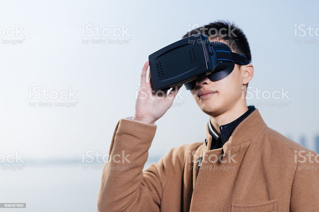 young asian man wearing VR near river in blue sky stock photo