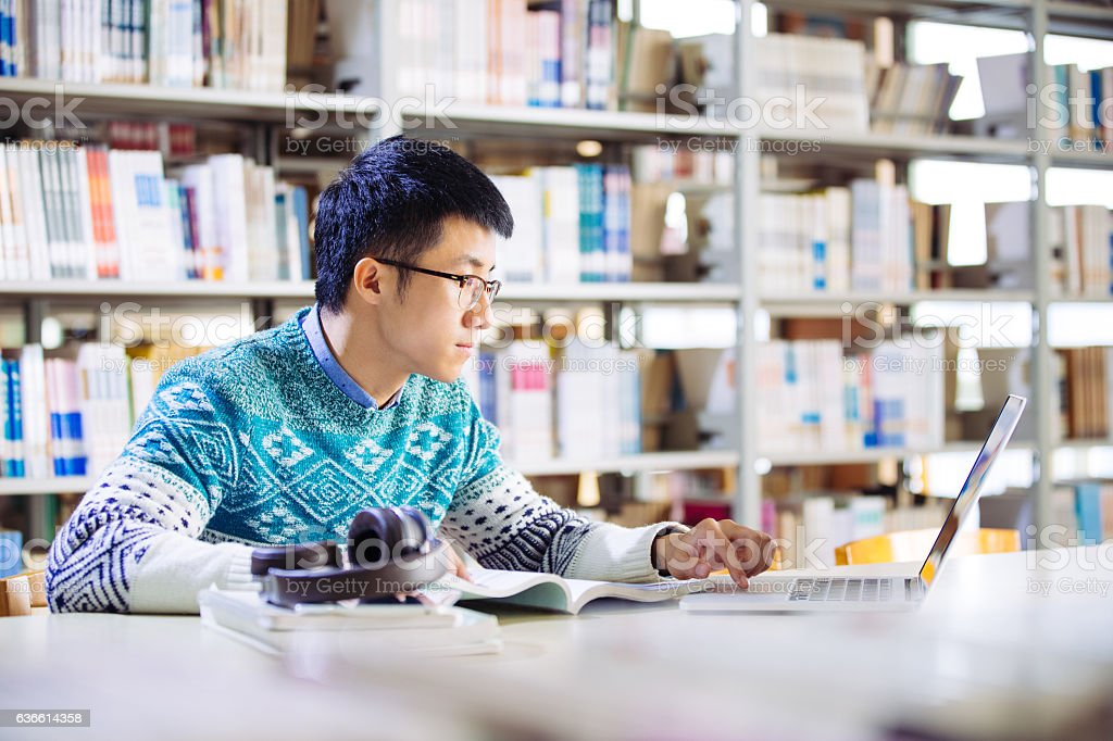 young asian man with laptop in library stock photo
