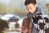 young asian man with mobile phone in modern city