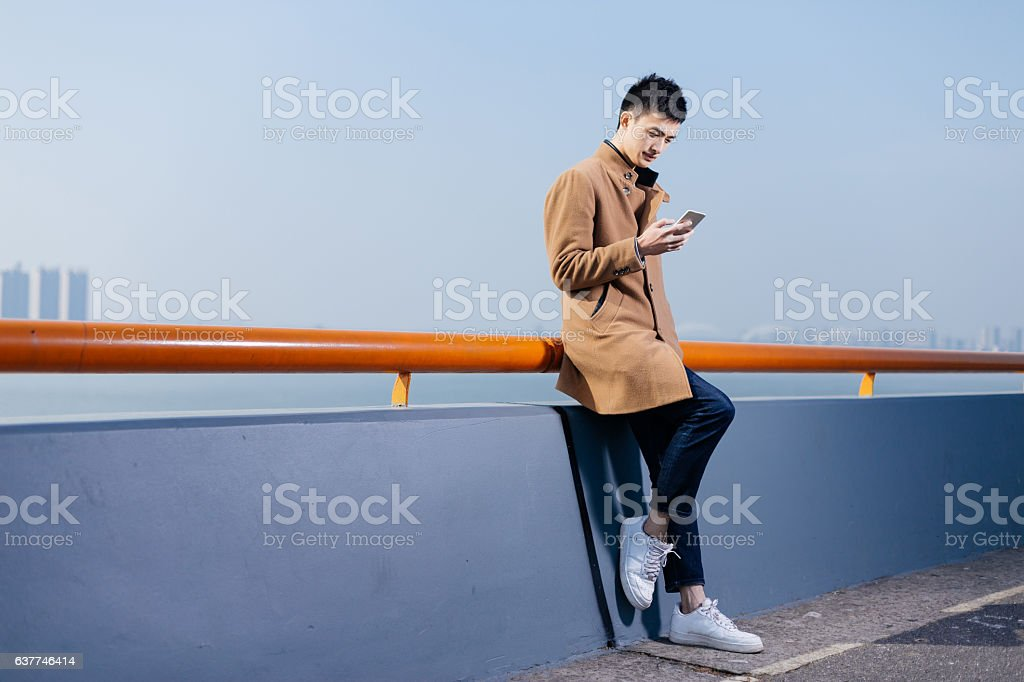 young asian man with mobile phone near river stock photo