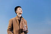 young asian man with mobile phone near river