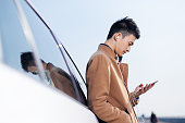 young asian man with mobile phone on road