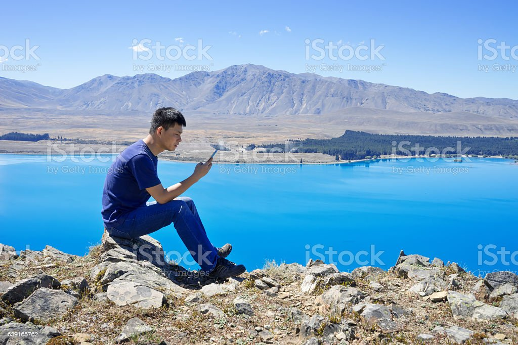 young asian man with mobile phone sitting by lake stock photo
