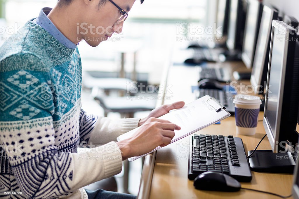 young asian man with pc and clipboard stock photo