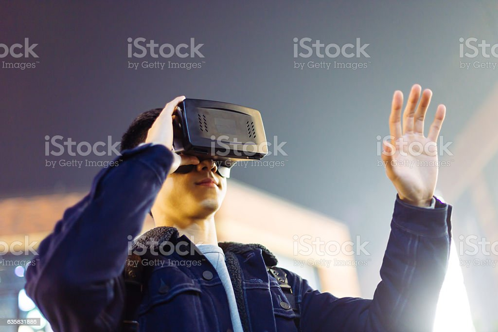 young asian man with VR on street at night stock photo