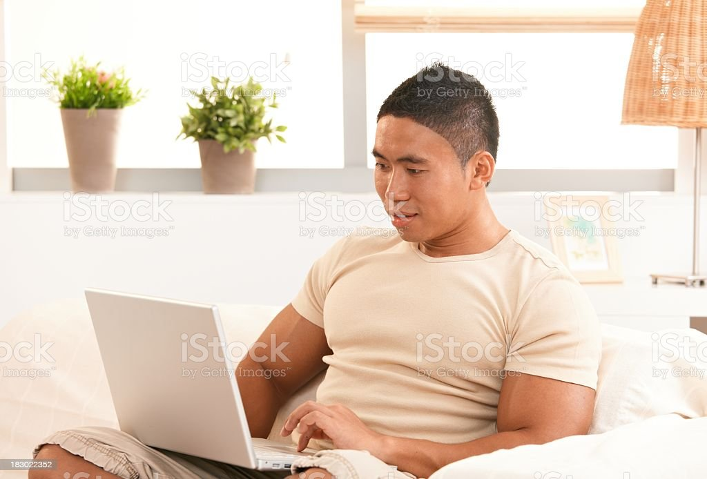 Young asian man working at home with computer royalty-free stock photo