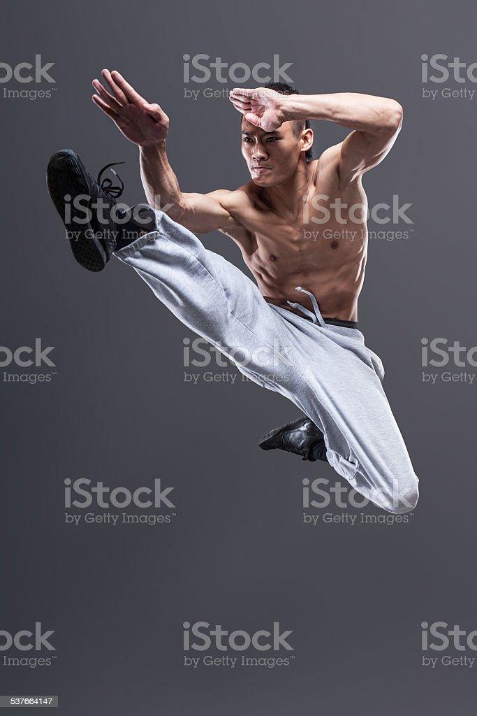Young asian man workout over grey background karate jump kick stock photo