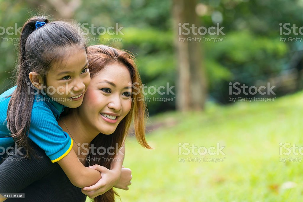 Young Asian Mother and School Age Daughter in City Park stock photo