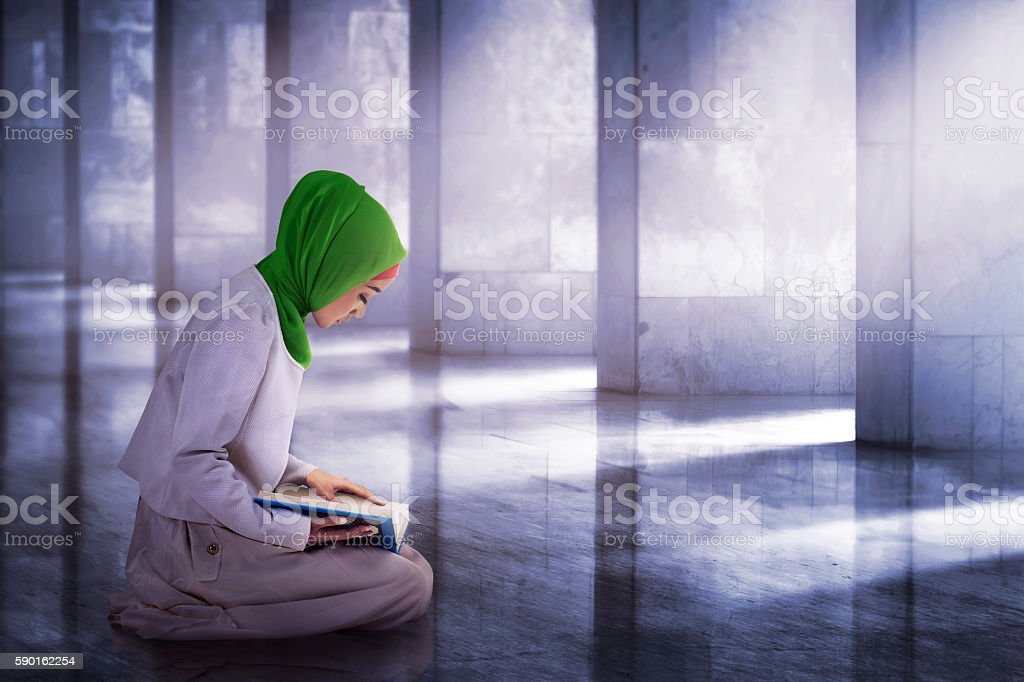 Young asian muslim woman reading the koran stock photo