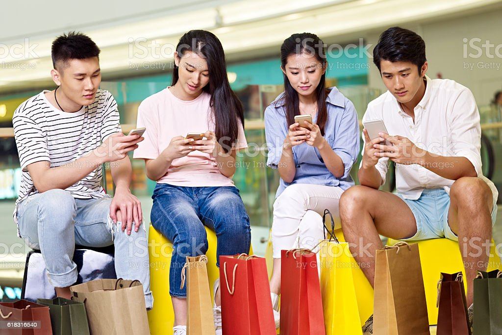 young asian people playing with mobile phones stock photo