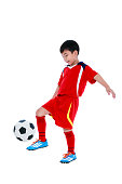Young asian soccer player with soccer ball. Studio shot.