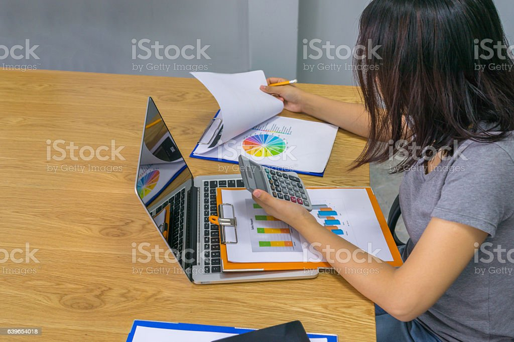 Young Asian supervisor double checking report and doing calculation stock photo