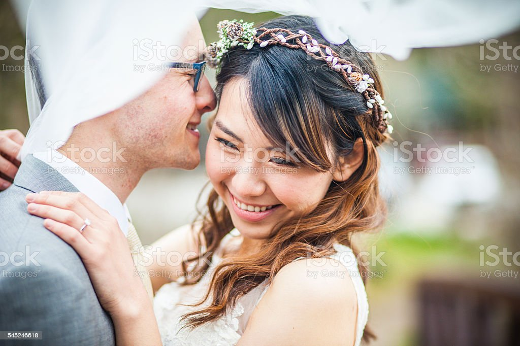 Young Asian Woman and Caucasian Man Wedding Photo stock photo